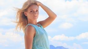 portret blondynki dziewczyny mienia włosy pod wiatrem przeciw chmurom zdjęcie wideo