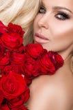 Portret blondynki kobieta, piękni zadziwiać spojrzenia i skóra długie włosy, perfect, utrzymuje twarz bukiet czerwone róże, v Zdjęcia Stock