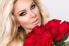 Portret blondynki kobieta, piękni zadziwiać spojrzenia i skóra długie włosy, perfect, utrzymuje twarz bukiet czerwone róże, v Zdjęcie Stock