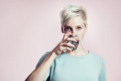Portret blondynki kobieta z szkłem woda, krótkiego włosy jaskrawy tło Fotografia Stock