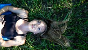 Portret blondynki młoda kobieta kłaść w trawie z długie włosy up i niebieskie oczy przyglądający z pokojowym wyrażeniem fotografia royalty free