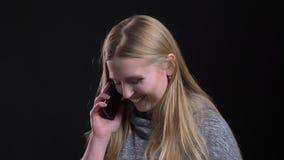 Portret blondynki prostowłosa dziewczyna opowiada poważnie na smartphone na czarnym tle zbiory wideo