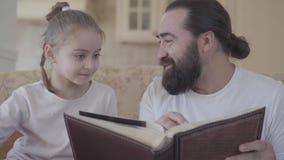 Portret brodaty mężczyzny obsiadanie na kanapa seansu książce jego mała córka zamknięta w górę Pojęcie szczęśliwa rodzina mały zbiory