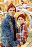 Portret brunet z jego syn pobliską żelazną strukturą w jesień parku fotografia royalty free