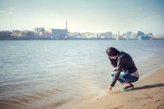 Portret brunetki dziewczyna w przypadkowych ubraniach rysuje na piasku Fotografia Royalty Free
