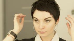 Portret brunetki kobieta robi hairstyling przodu lustra zakończeniu up Stawia czoło pięknej kobiety wzruszającego włosy i patrzeć zbiory