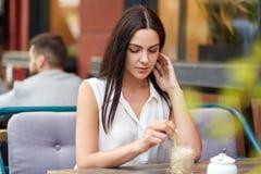 Portret brunetki poważna kobieta rozważnego wyrażenie, pije koktajl w plenerowej kawiarni, czeka partnera biznesowego, cieszy się fotografia stock