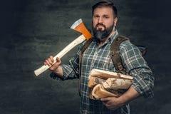 Portret brutalna brodata myśliwy samiec trzyma cioskę na jego shoul Zdjęcie Stock