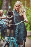Portret córka z blondynka włosy na rowerowej przejażdżce z ich ślicznym małym spitz psem w parku i matka Obraz Royalty Free