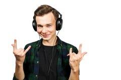 Portret caucasian Biały młody facet słucha muzykę w telefon skale Przystojny mężczyzna ubierał w czarnej koszulce i zieleni zdjęcia royalty free