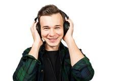 Portret caucasian Biały młody facet słucha muzykę w telefonach Przystojny mężczyzna ubierał w czarnej koszulce i zielonej szkocki fotografia stock