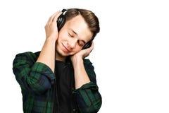 Portret caucasian Biały młody facet słucha muzykę w telefonach z oczami zamykającymi Przystojny mężczyzna ubierający w czarnej ko zdjęcia stock