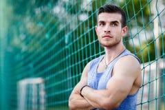 Portret caucasian mięśniowy mężczyzna opiera na sport futbolowych sieciach Zdjęcia Royalty Free