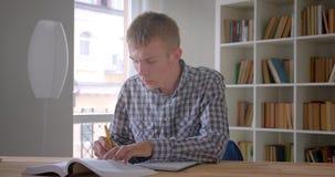 Portret caucasian studencka pisze praca domowa jest koncentrujący i baczny przy biblioteką zbiory