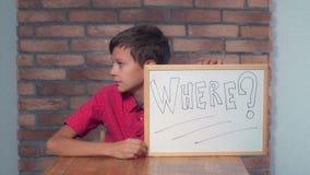 Portret chłopiec pokazuje whiteboard z handwriting słowa whe fotografia royalty free