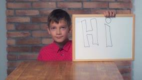Portret chłopiec pokazuje whiteboard z handwriting słowem cześć fotografia stock