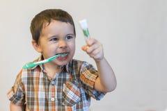 Portret chłopiec szczotkuje zęby w kąpielowym pokoju, dzieciak jest ubranym pyjamas z czyścić jego zęby w ranku, dziecka zdrowie zdjęcia stock
