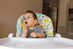 Portret chłopiec łasowania dziecka śliczny ciastko pierwszy jedzenie dla dzieci 10 miesięcy berbeć chłopiec uczenie żyć z ząb bry Fotografia Stock