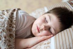 Portret chłopiec dosypianie w łóżkowym dniu Zdjęcia Royalty Free