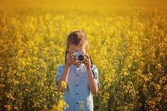 Portret chłopiec fotograf z kamerą na zmierzchu koloru żółtego pola tle Obraz Stock