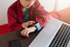 Portret chłopiec jest ubranym elektronicznego zegarek patrzeje at the time w czerwonym koszulowym obsiadaniu przy drewnianym stoł zdjęcia stock