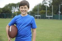 Portret chłopiec mienia piłka Na Szkolnej Futbolowej smole Obrazy Stock