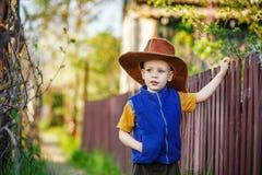 Portret chłopiec pozycja w dużym kapeluszu w drewnianym fen troszkę Obrazy Royalty Free