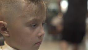 Portret chłopiec w dziecko fryzjera męskiego sklepie Śliczna chłopiec podczas gdy dzieci ciie włosy w fryzjerstwo salonie z blisk zbiory wideo