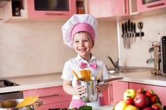 Portret chłopiec w kapeluszu szef kuchni i fartuch Mały kucharza szef kuchni w kuchennym narządzanie spaghetti zdjęcia stock