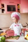 Portret chłopiec w kapeluszu szef kuchni i fartuch Mały kucharza szef kuchni w kuchni Zdjęcia Royalty Free
