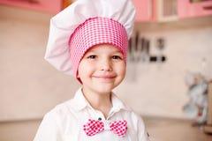 Portret chłopiec w kapeluszu szef kuchni i fartuch Mali szefów kuchni kucharzi w kuchni Portret pomaga przy kitch śliczna chłopie obrazy stock