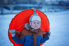 Portret chłopiec z tubingiem w śniegu, wintertime, szczęścia pojęcie Obrazy Stock