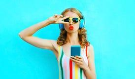 Portret ch?odno dziewczyny podmuchowe czerwone wargi wysy?a cukierki powietrza buziaka mienia dzwoni? s?uchanie muzyka w bezprzew fotografia royalty free
