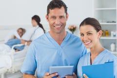 Portret chirurdzy z doktorskim uczęszcza pacjentem na tle Zdjęcie Stock
