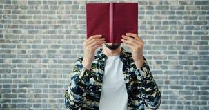 Portret chuje twarz za książkowy ono uśmiecha się na ściany z cegieł tle radosny mężczyzna zbiory