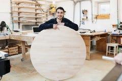 Portret cieśla pozycja w jego woodwork cieśli pracownianym warsztacie Mężczyzna trzyma drewnianą round deskę dla teksta zdjęcie stock