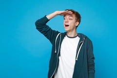 Portret ciekawy młody człowiek trzyma rękę przy czoło przyglądającą daleką odległością odizolowywającą na błękicie w przypadkowyc zdjęcia stock