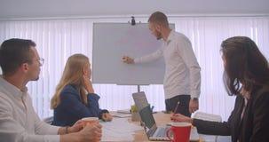 Portret cztery collleagues spotyka w biurze indoors Biznesmen pisze na whiteboard zdjęcie wideo