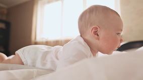 Portret cztery miesięcy dziecka stary lying on the beach na jego żołądku na łóżko domu zbiory
