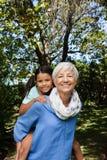 Portret daje piggyback wnuczka przeciw drzewom uśmiechnięta babcia Obraz Royalty Free