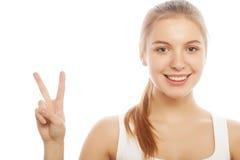 Portret daje pokoju znakowi szczęśliwa młoda kobieta fotografia stock