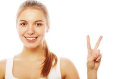 Portret daje pokoju znakowi szczęśliwa młoda kobieta zdjęcia royalty free