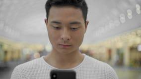 Portret dat van Aziatische mannelijke het scrollen telefoon op grote wandelgalerijachtergrond wordt geschoten stock footage