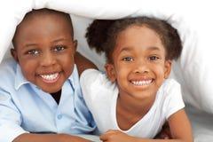 Portret dat van etnische siblings op bed ligt royalty-vrije stock fotografie