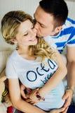 Portret dat van het verwachten van paar dat, baby in buik samen omhelst gelukkig lacht Royalty-vrije Stock Foto