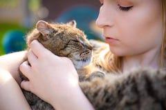 Portret dat van jonge vrouw een kat in haar wapens houdt Mooie dame die weinig zoet, aanbiddelijk katje houden stock afbeelding