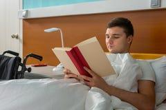Portret dat van mannelijke patiënt in het het ziekenhuisbed ligt en a leest Stock Foto