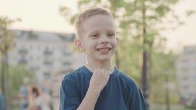 Portret de beau garçon de sourire en parc Sun et nature gentille Mouvement lent banque de vidéos