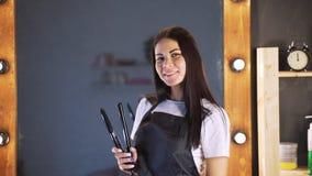 Portret del peluquero hermoso sonriente de la mujer con el delantal negro que mira la cámara mientras que detiene al peluquero pr almacen de metraje de vídeo