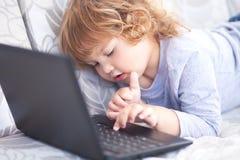 Portret del primo piano di poca ragazza dei capelli del ricciolo che lavora al computer portatile Immagini Stock